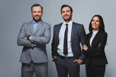 smiling businesspeople looking at camera isolated on grey