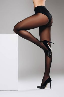 Woman in black pantyhose leaning on white box