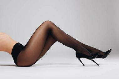 Woman in black pantyhose and heel shoes lying on white background