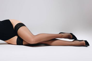Woman in black stockings and heel shoes lying on white background
