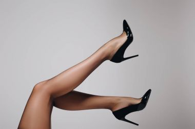 Female legs in black stockings and heel shoes isolated on grey background