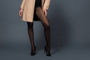 Cropped view of woman wearing black tights and beige trench on dark background