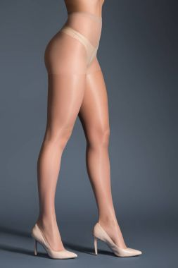 Female legs in beige pantyhose and shoes on dark background