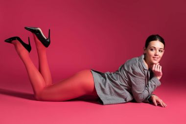 sexy girl in red tights and grey jacket lying on red background