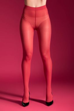 Female thin legs in red nylon tights on red background