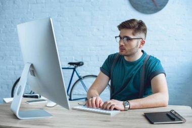 handsome young man in eyeglasses working with desktop computer