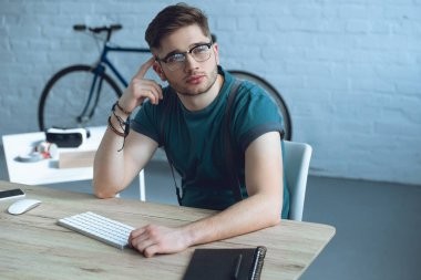 handsome pensive freelancer in eyeglasses looking away while sitting at workplace