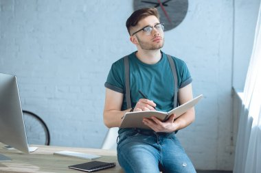 pensive young man in eyeglasses looking away while writing in notebook at home office