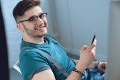 Veselý mladý muž pomocí smartphone a usmívá se na kameru