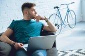 pohledný mladý muž pomocí přenosného počítače a hledat dál, zatímco sedí doma