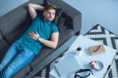 pohled z vysoké úhlu mladého muže ležet na gauči a koukal doma
