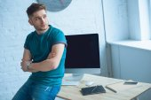 Fotografie handsome young man with crossed arms sitting on table and looking away while working at home