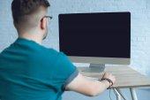 Az ember nézi a számítógép képernyőjén a táblázat hátulnézet