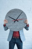 Fotografie Muž, který držel velké hodiny před obličejem