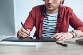 Fotografie Young illustrator sitting by table with graphic tablet