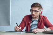 Fotografie Freelancer man in headphones drawing with graphic tablet by table with computer