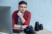 Fiatal szakállas ember által dolgozó asztal, kamera és a számítógép