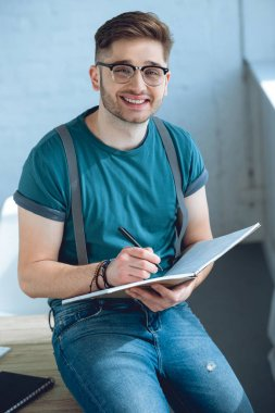 Handsome young man in eyeglasses taking notes and smiling at camera stock vector
