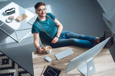 high angle view of handsome young man in eyeglasses smiling at camera while sitting at workplace at home office