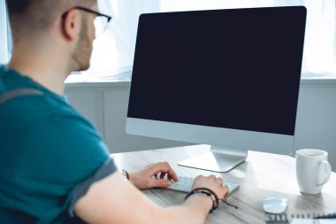 cropped shot of young freelancer using desktop computer with blank screen
