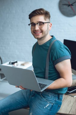 handsome young man in eyeglasses holding laptop and smiling at camera