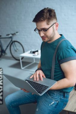 handsome young freelancer in eyeglasses using laptop at home