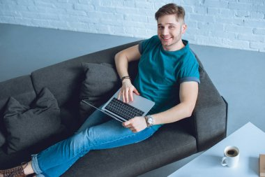high angle view of handsome young freelancer using laptop and smiling at camera