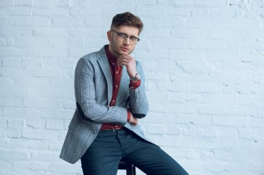 Handsome young man wearing suit and glasses sitting in front of brick wall