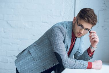 Attractive bearded man wearing suit and glasses leaning on windowsill