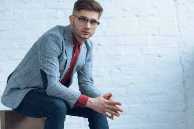 Attractive bearded man wearing suit and glasses and sitting in front of brick wall