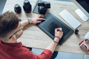 Freelancer man drawing with graphic tablet by table with computer
