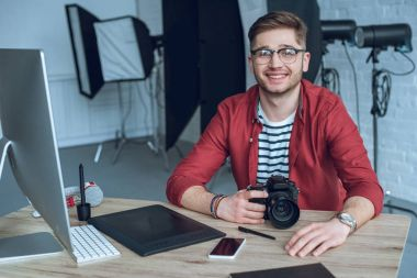 Happy freelancer man sitting by working table with camera and graphic tablet