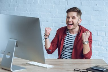 Excited freelancer at the table with computer screen