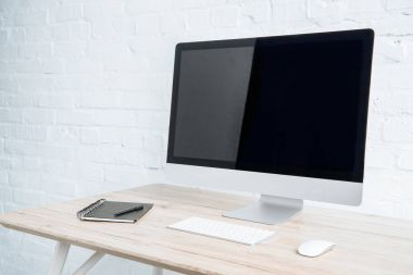 Blank computer screen with notebook on table in light office
