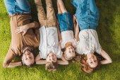 Fotografia vista superiore della famiglia felice con due bambini che si trovano sul prato e sorride alla macchina fotografica