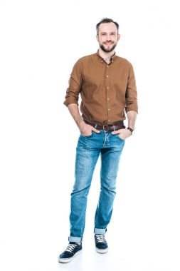 full length view of handsome bearded man standing with hands in pockets and smiling at camera isolated on white