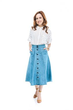 full length view of beautiful woman standing with hands in pockets of denim skirt and smiling at camera isolated on white