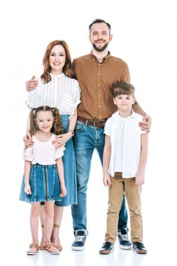 full length view of happy family with two kids standing together and smiling at camera isolated on white