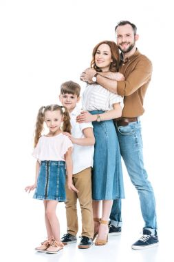 full length view of happy family with two children standing together and smiling at camera isolated on white