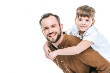 happy father piggybacking little son and smiling at camera isolated on white