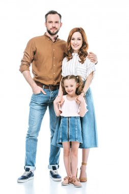 happy parents with adorable little daughter standing together and smiling at camera isolated on white