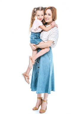 happy mother carrying adorable little daughter and smiling at camera isolated on white