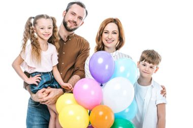 happy family with two kids holding colorful balloons and smiling at camera isolated on white