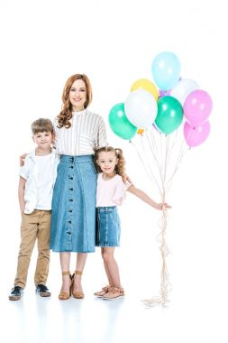 Happy mother and two kids with colorful balloons standing together and smiling at camera isolated on white stock vector