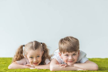 happy little kids lying on lawn and smiling at camera on grey