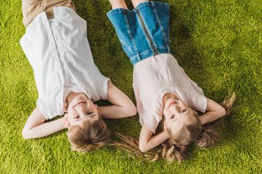 top view of happy children lying on lawn and smiling at camera