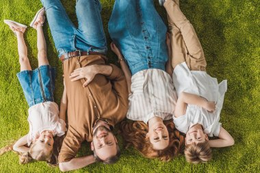 top view of happy family lying on lawn and smiling at camera