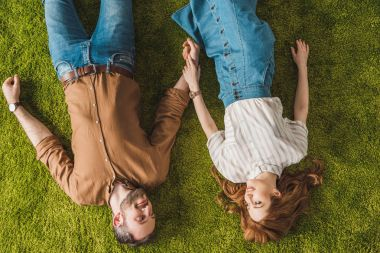 top view of happy couple lying on green lawn and smiling each other