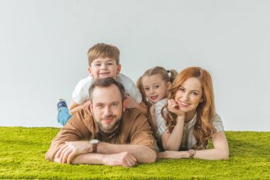 cheerful family with two kids lying on lawn and smiling at camera on grey