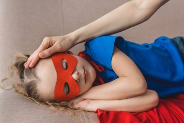 cropped shot of mother touching forehead of little daughter in superhero costume sleeping on sofa